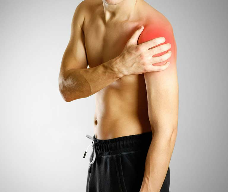 a boy holding his in pain left upper arm