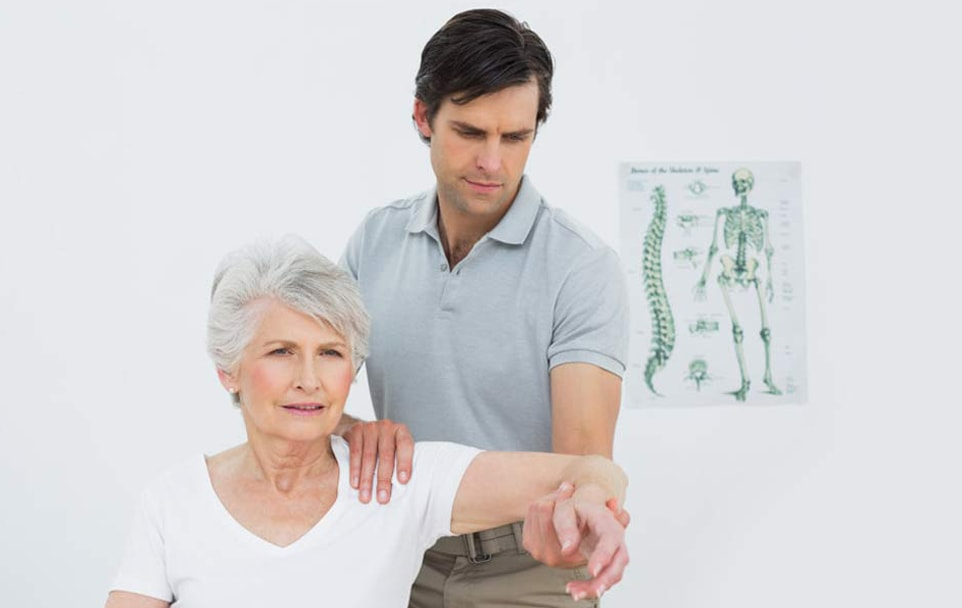 a doctor holding the patient's left arm for physical therapy
